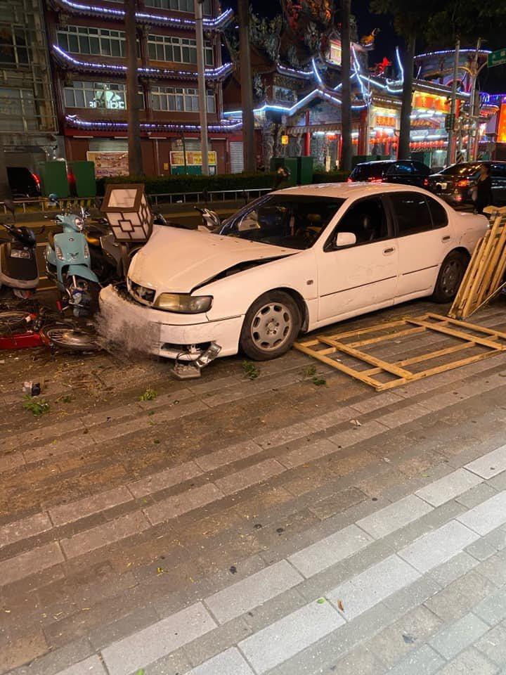屏東市慈鳳宮前,一部白色自轎車不明原因失控逆向衝上人行道,導致多部路邊機車、腳踏...