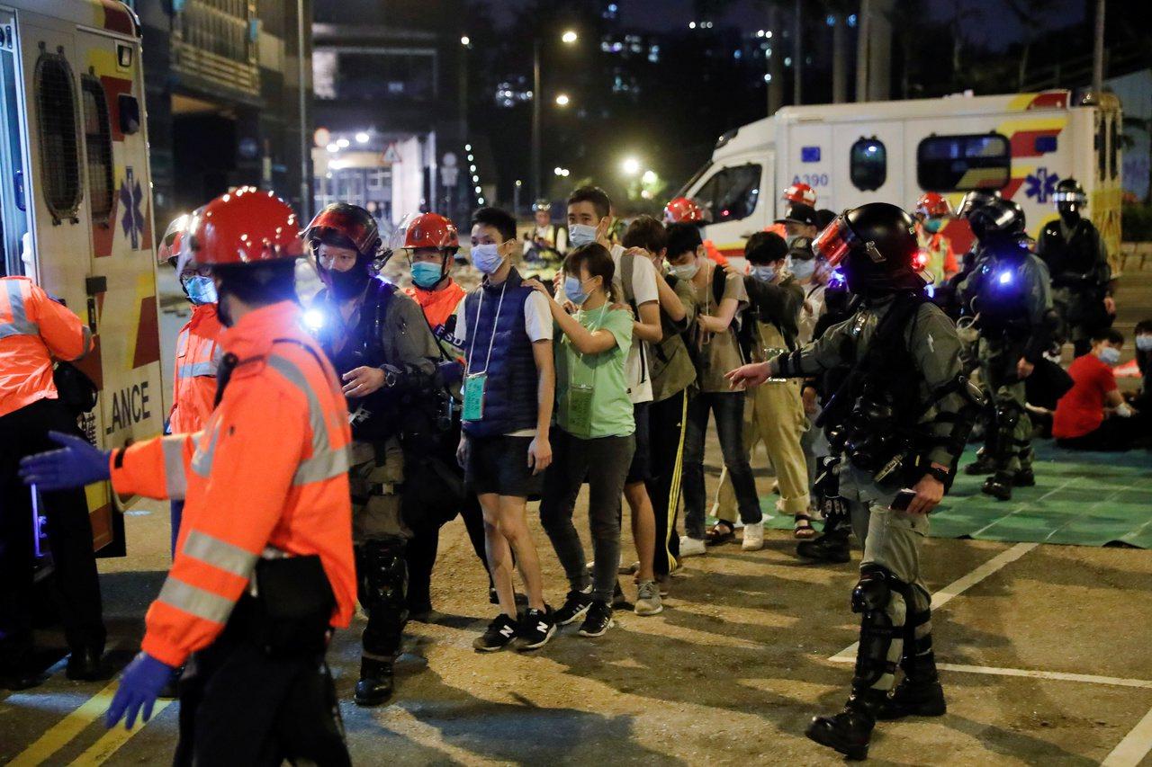 香港警察17日入夜後包圍理工大學,要求留守者投降。圖為一批示威者18日在警方押送...