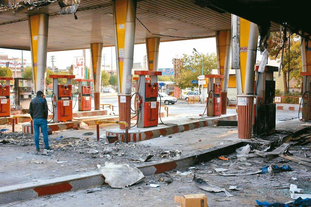 一名男子十七日查看伊朗首都德黑蘭近郊一座遭反政府示威者破壞的加油站。 (法新社)