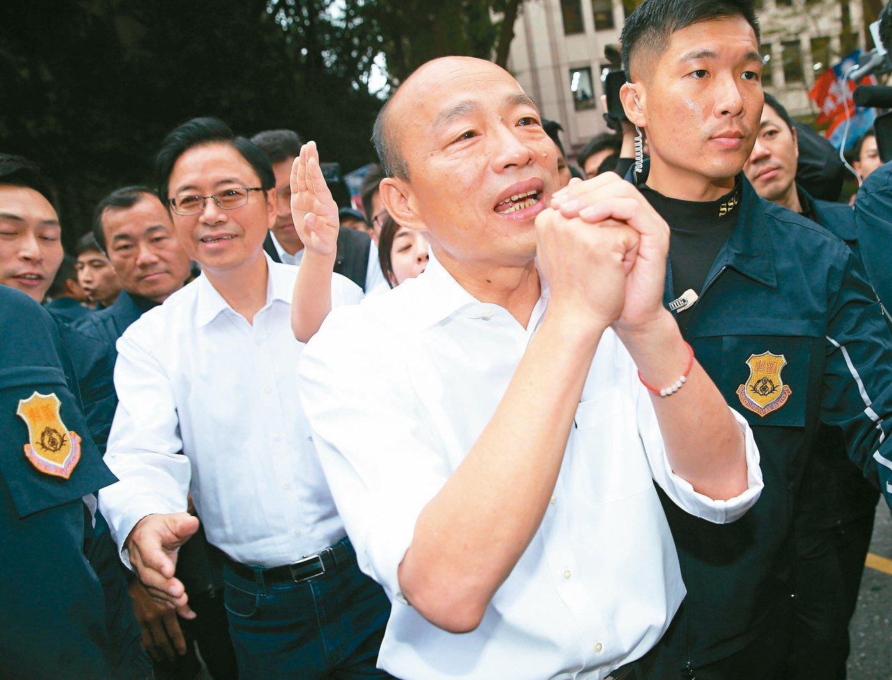 國民黨正副總統參選人韓國瑜(前右)與張善政(前左)完成登記後,步出中選會向支持者...