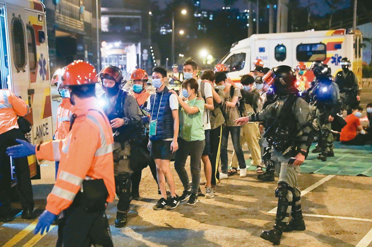 香港警察十七日入夜後包圍理工大學,要求留守者投降。圖為一批示威者十八日在警方押送...