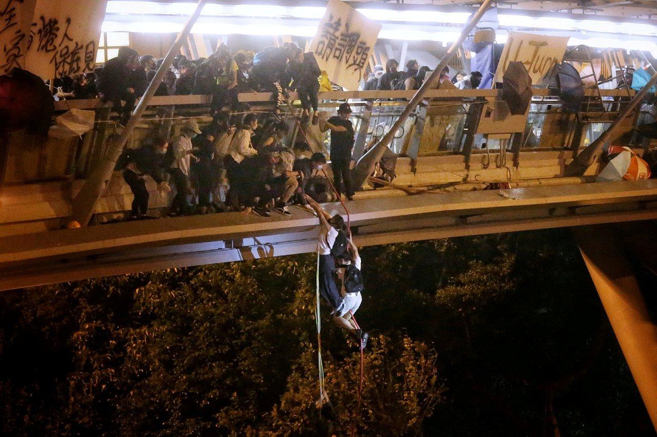 路透報導,進占香港理工大學的部分反政府示威者18日從校內一座橋垂降到數公尺之下的...