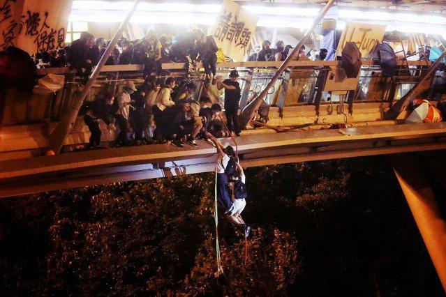 「命懸一線。」18日晚,受困香港理大校園的部分示威者,透過簡易繩索,試圖悄悄突破...