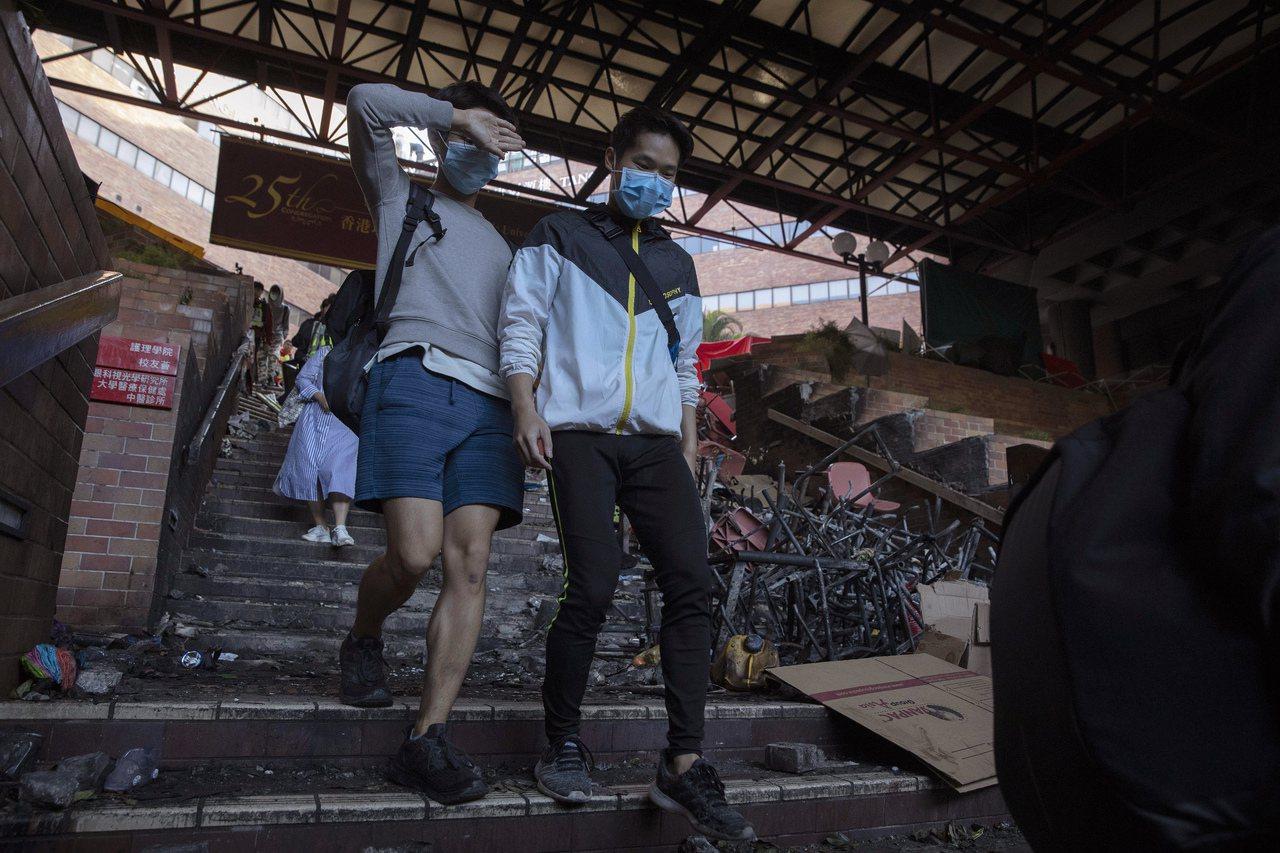 19日多名學生和示威者陸續離開理大。美聯社