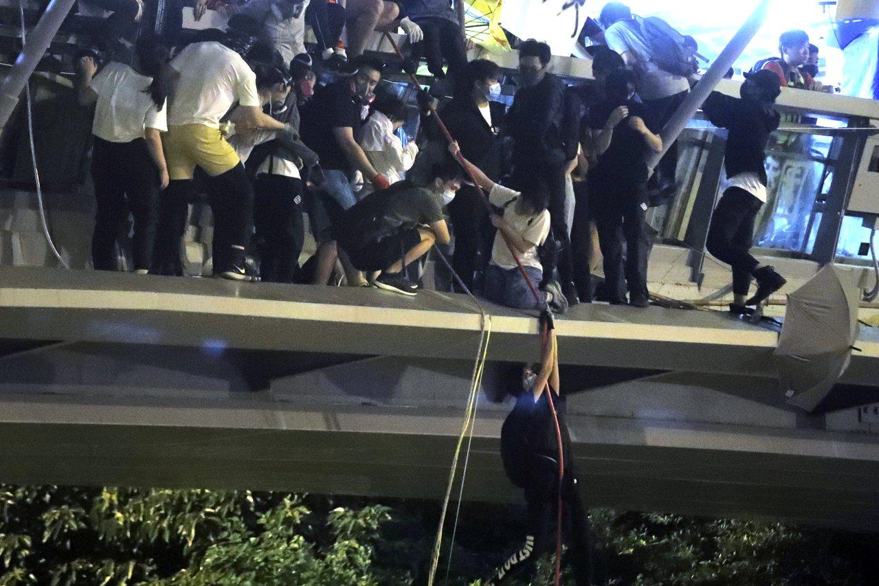 周一晚間,約數百示威者則從連接8期校園的行人天橋上,沿著繩索垂降到漆咸道南天橋的...