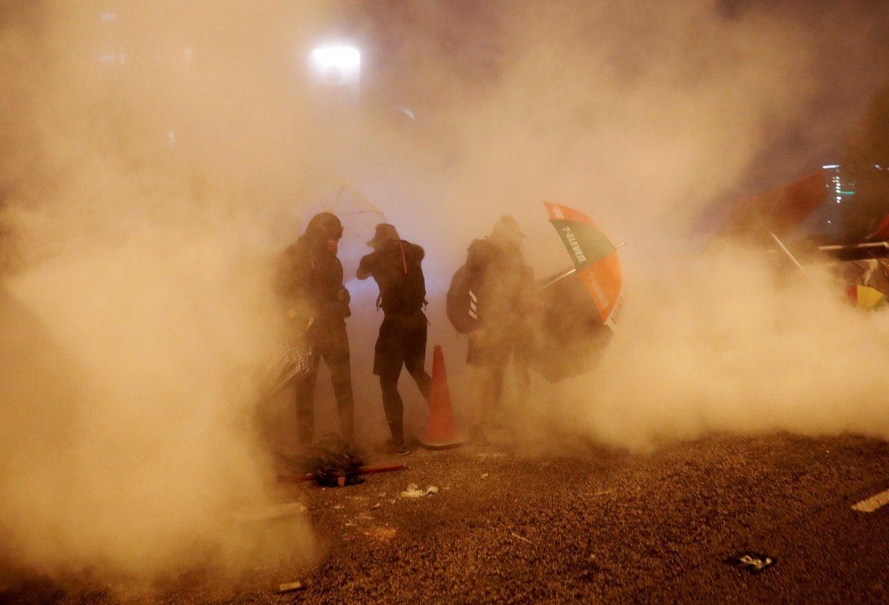 香港示威者18日在香港理工大學附近的警民衝突中,籠罩在港警發出的催淚瓦斯中。路透