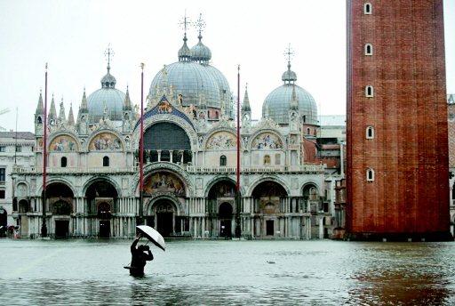 威尼斯景點聖馬爾谷廣場淹水,一名攝影師邊撐傘邊取景。 美聯社