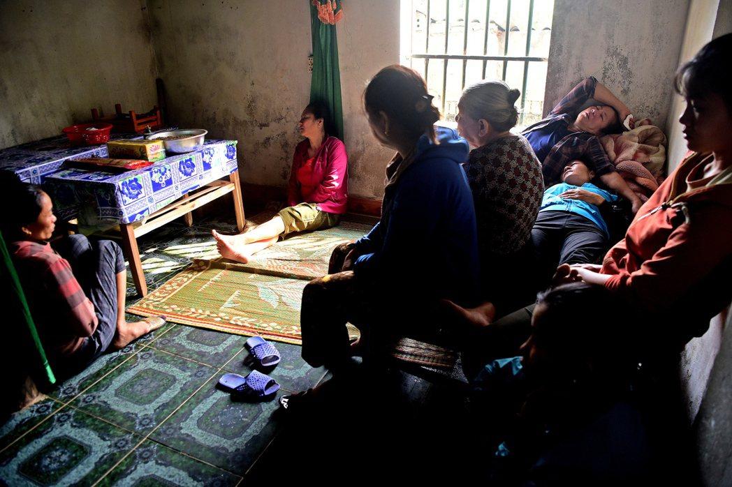 英國貨櫃屍案一名罹難者的家屬和鄰居,5日聚在越南義安省家中。(歐新社)