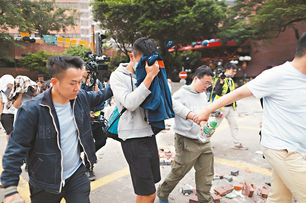 投降一名向警方投降的示威者,十九日用外套遮臉被帶離理大。 歐新社