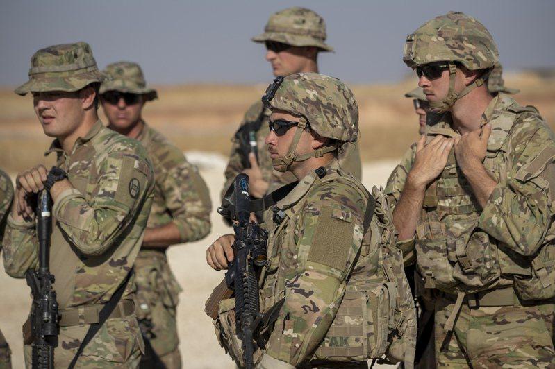 國防情報局指出,川普下令從敘利亞撤軍,讓擴散恐怖主義的伊斯蘭國增強實力。圖為一群美軍在敘利亞東北部等待搭乘軍車。 美聯社