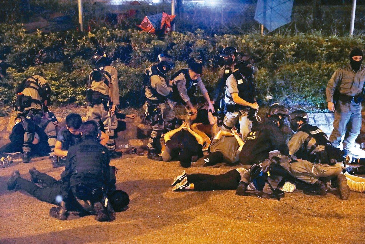 企圖逃離香港理工大學的抗議者19日被港警逮捕後,趴在地上。 路透