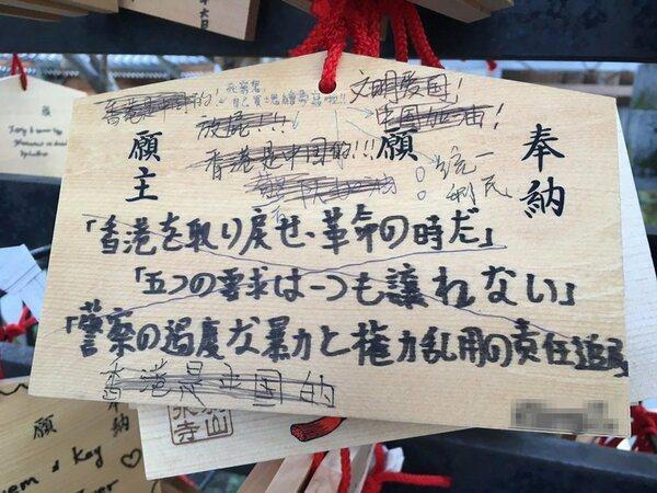 以日文寫下「取回香港,革命時刻到來,五個要求,一個也不讓,追究警察過度暴力及濫權...