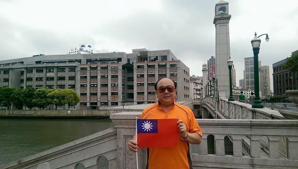 吳斯懷2015年到上海旅遊,在四行倉庫前「秀國旗」拍照。圖/引自吳斯懷臉書
