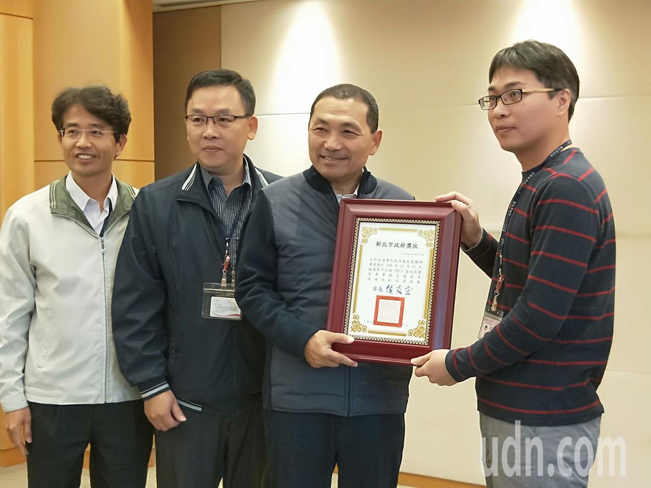 新北市長侯友宜(右二)表揚辦事員林意騰(右一),感謝他救回同事性命。記者施鴻基/...