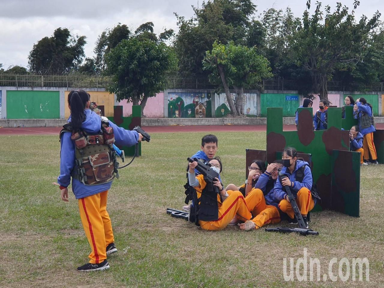 校園中出現「雷射槍戰」課程,學生們穿著迷彩背心、配置雷射槍枝,在操場上激烈對戰,...