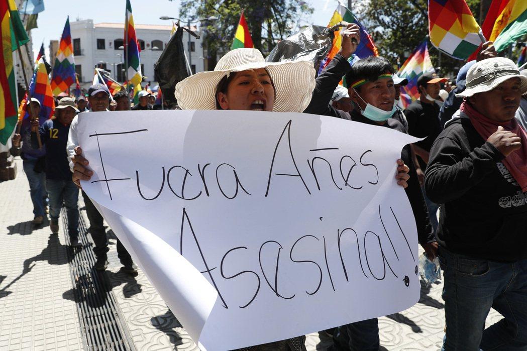 玻利維亞流亡總統莫拉萊斯的支持者18日在哥查班巴市發起示威,示威者手中標語寫著「...