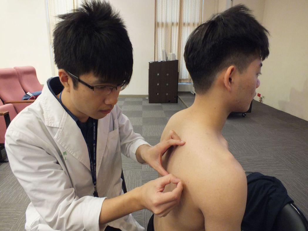 醫師楊潤(左)說明,陳姓大學生(右)勤練重訓,透過針灸激痛點治療兼保養,讓運動生...