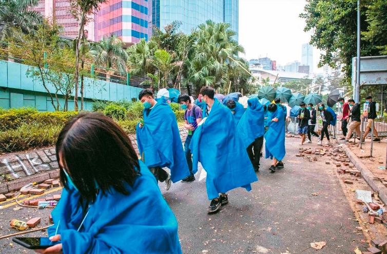 被港警圍困三天的香港理工大學示威者,接受警方條件後昨自首陸續從校園撤出。(法新社...