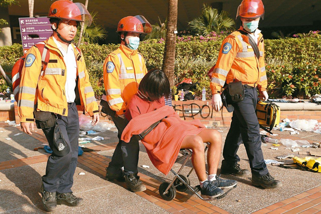一名疑似受傷的示威者在醫護人員陪同下,坐著輪椅離開理大。 (歐新社)