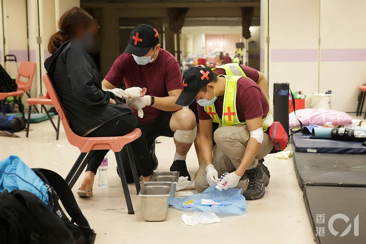 11月20日晚,最後一批義務急救員撤離前,仍幫校內留守的示威者包紮傷口。(李澤彤...