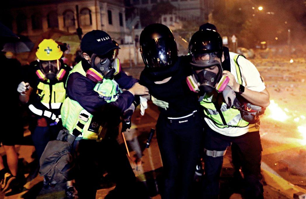 16日,醫護人員攙扶在理工大學的衝突中受傷的示威者。 圖/路透社