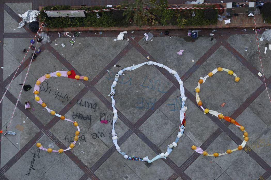 示威者在理工大學內與港警鏖戰數日,並排出SOS字樣。 圖/歐新社