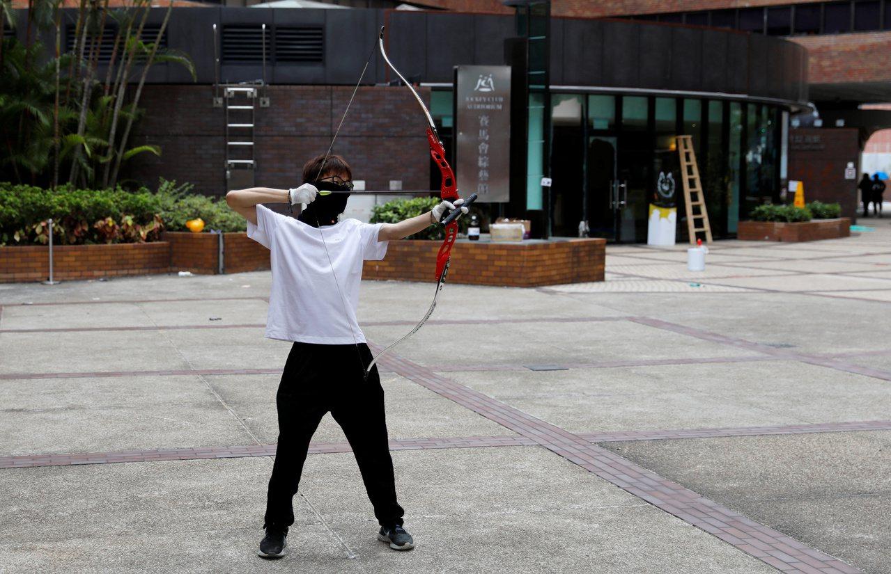 一名示威者在理大校區內練習射箭。理大被港警重重包圍已有5日,21日仍有至少50名...