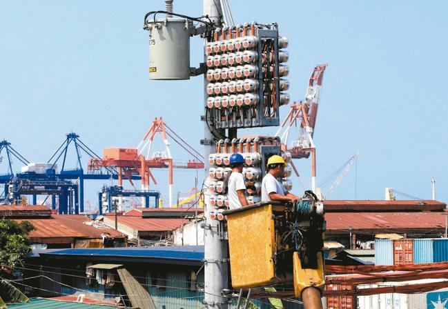 電力公司員工在馬尼拉大都會區的電線桿進行維修作業畫面。 路透