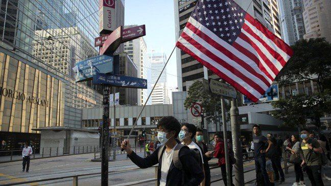 一位香港青年在20日的抗議活動中,高舉美國國旗。美聯社