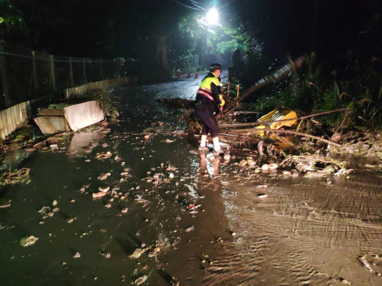 基隆市警二分局信義派出所員警昨晚在月眉路發現土石和樹木滑落影響交通,將部分樹木及...