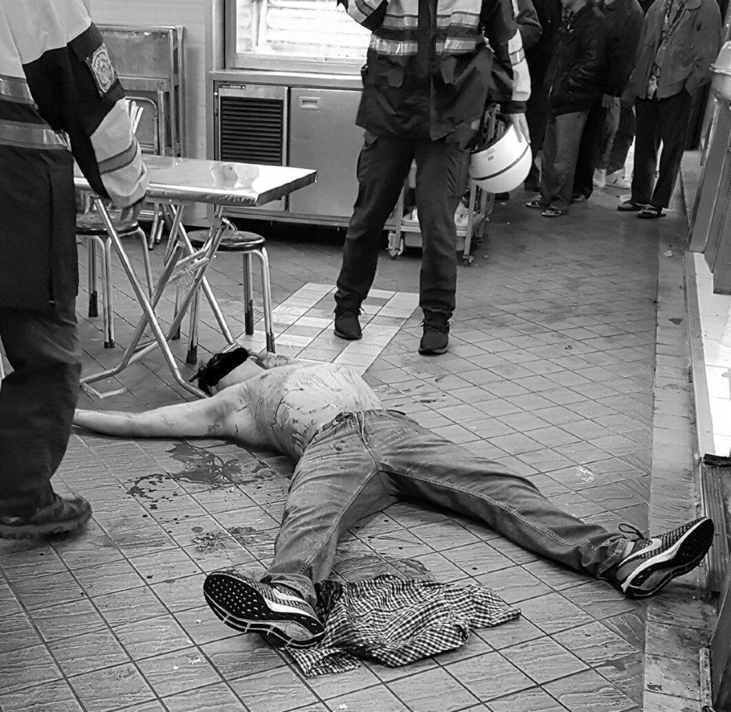 王男被羅用剪刀刺傷背部及左耳,導致血流如注、躺臥店外騎樓。記者李隆揆/翻攝