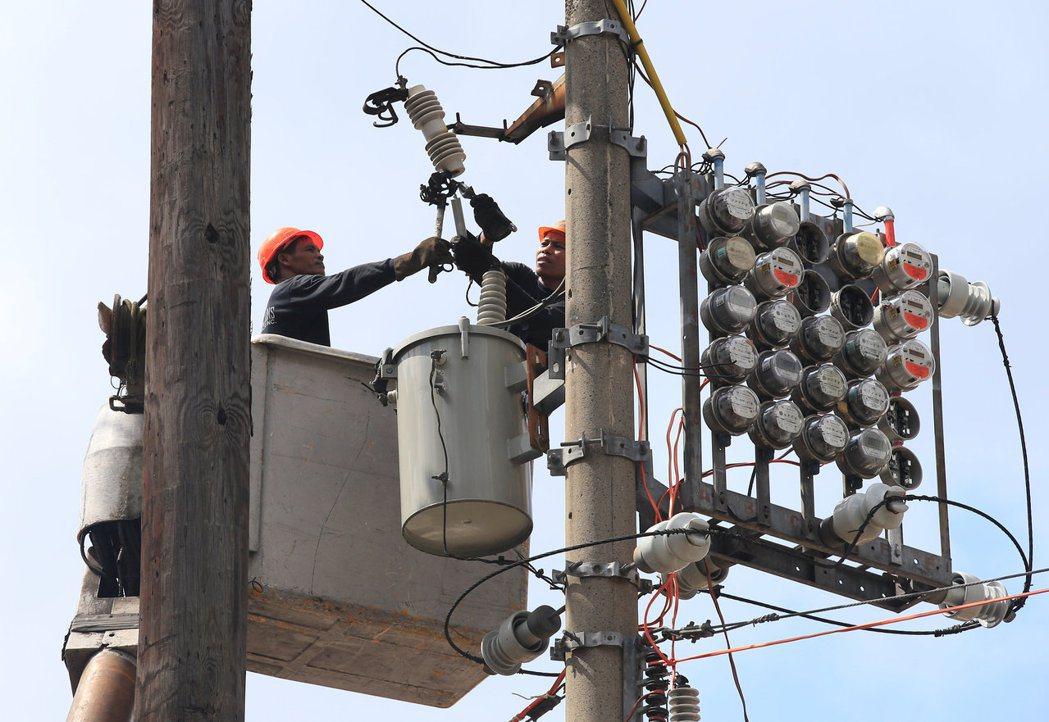 電力公司員工在馬尼拉大都會區的電線桿進行維修作業畫面。路透
