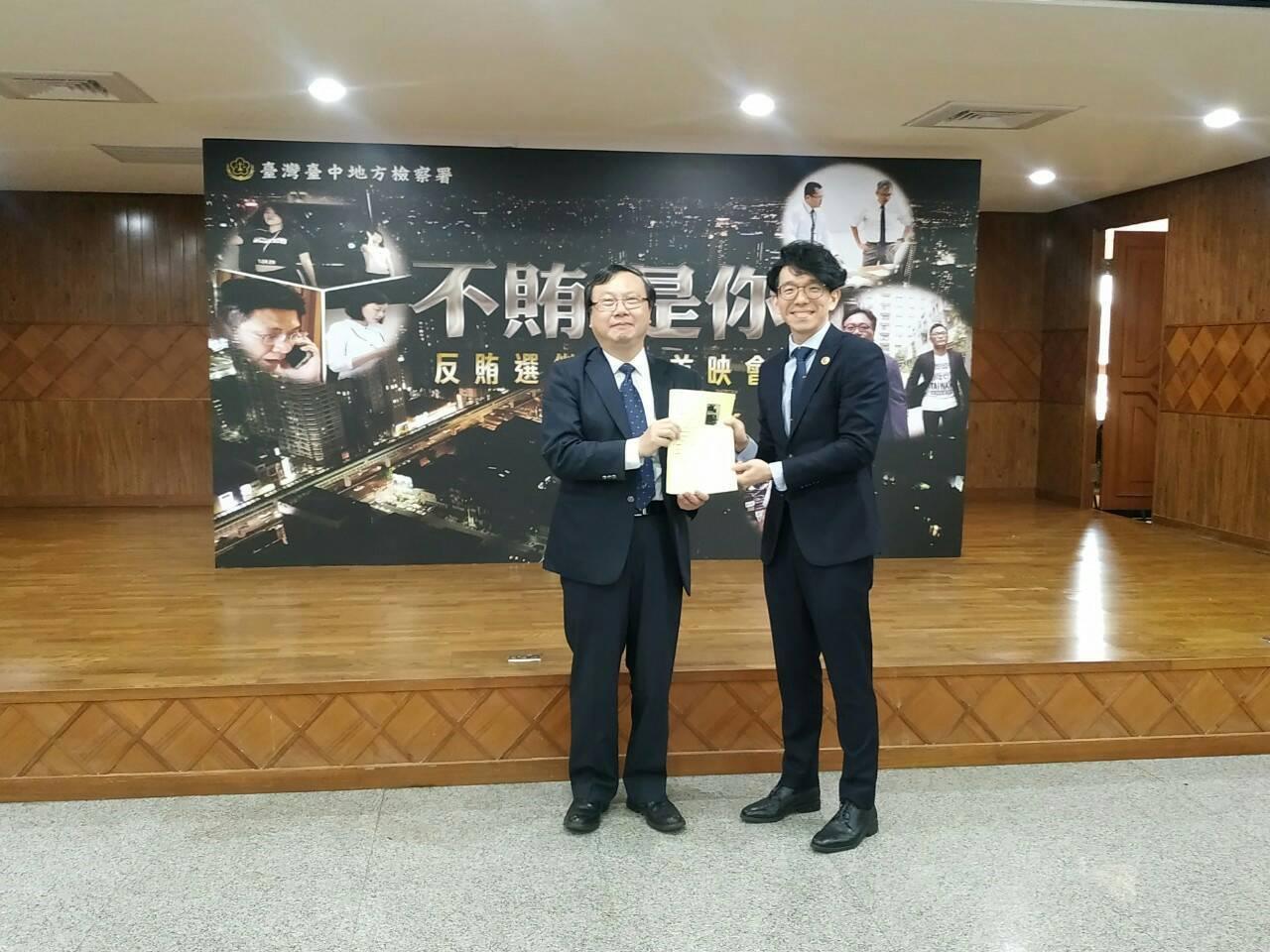 檢察官張凱傑(右)將劇本分鏡圖送給檢察長陳宏達(左),現場歡笑不斷。圖/台灣台中...