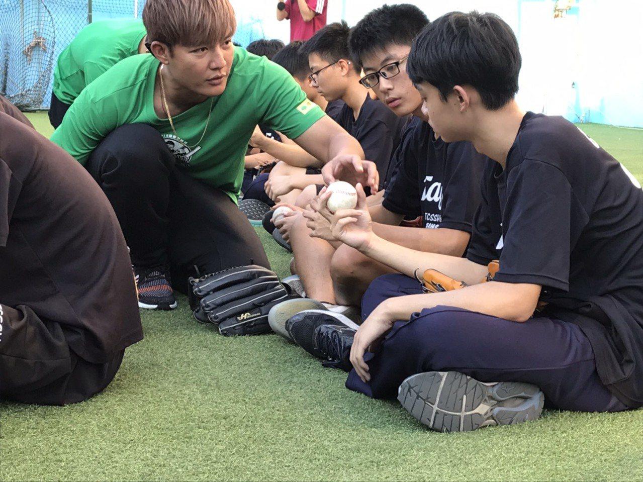 王維中在棒球教室細心指導球員握球方式。圖/國泰金控提供