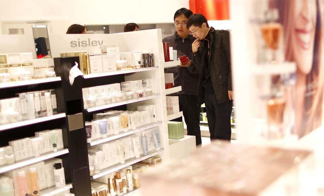 中國大陸年輕男性開始愈來愈重視外表,投入化妝的行列。圖為年輕男性正在逛化妝品免稅...
