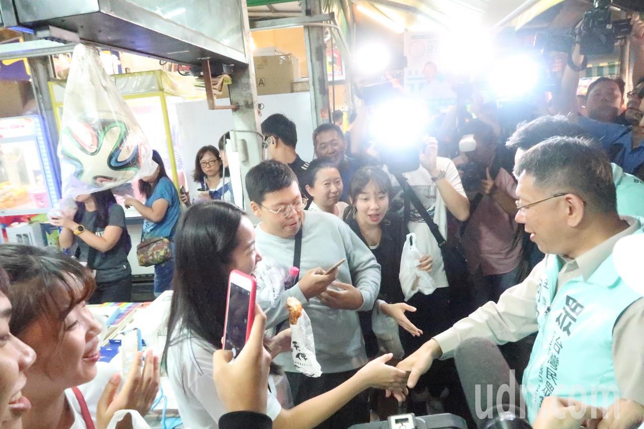 台灣民眾黨主席柯文哲(右)到瑞豐夜市陪黨籍立委參選人掃街拜票,受到群眾熱情回應。...