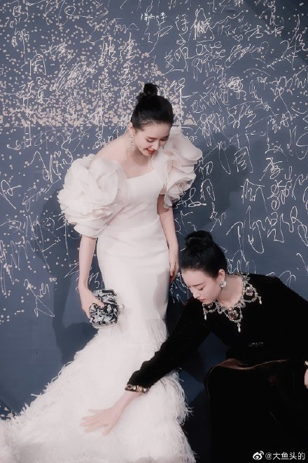劉詩詩因裙擺過長,倪妮還蹲下身幫她整理,雙姝黑白配超搶眼。圖/摘自微博