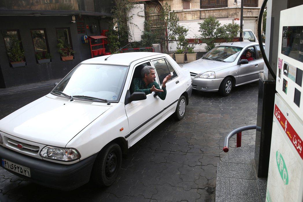 伊朗政府宣布油價調漲後,民眾在加油站排隊等候加油。(路透)