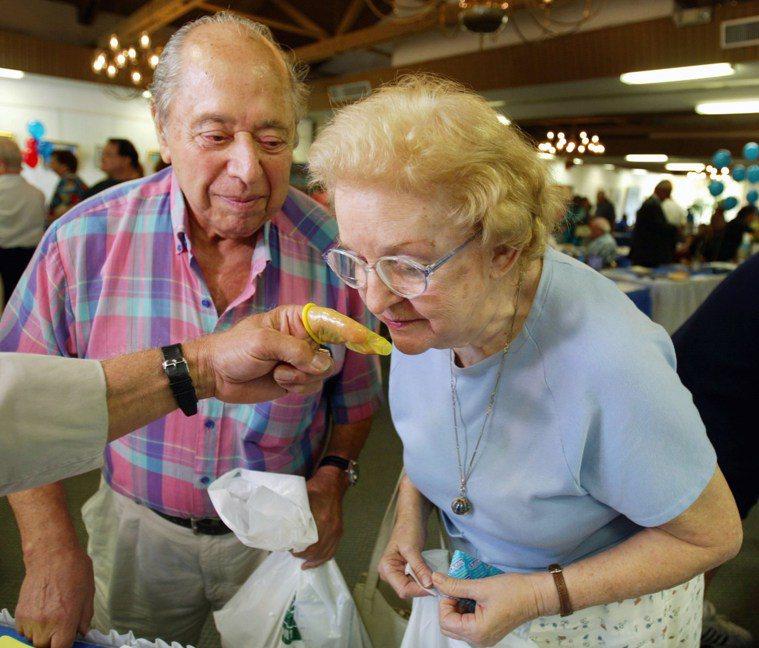 步入老年未必不能過得很「性」福。圖為一對耆老夫婦在防治性病活動上,好奇聞著有杏仁...