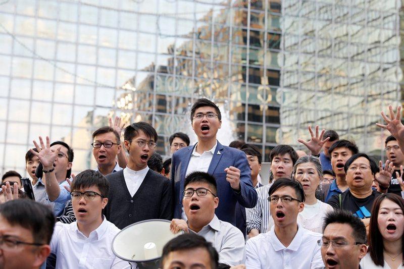 泛民主派當選人與民眾於香港理工大學外聲援受困示威者,要求港警放人。 圖/路透社