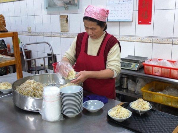 看著店家人員先鬆動一大鍋的豆菜麵,接著抓進一碗一碗裡,動作非常熟練。