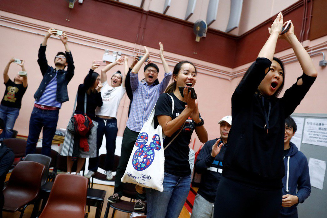 市民在投票站歡呼慶祝泛民派候選人得勝。 圖/路透社