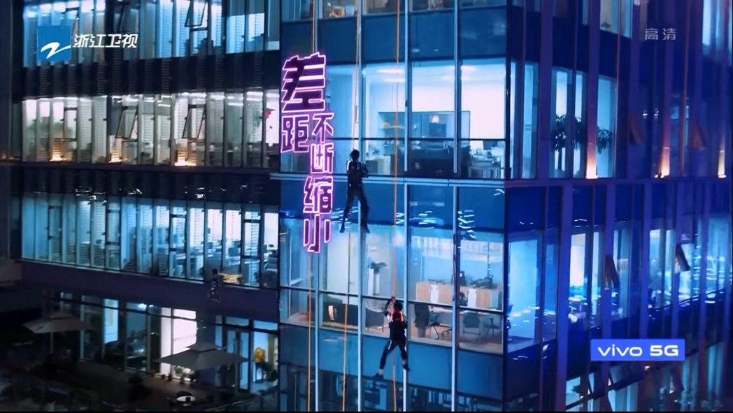 《追我吧》節目參賽者從高樓外部攀爬。 圖/擷自Youtube