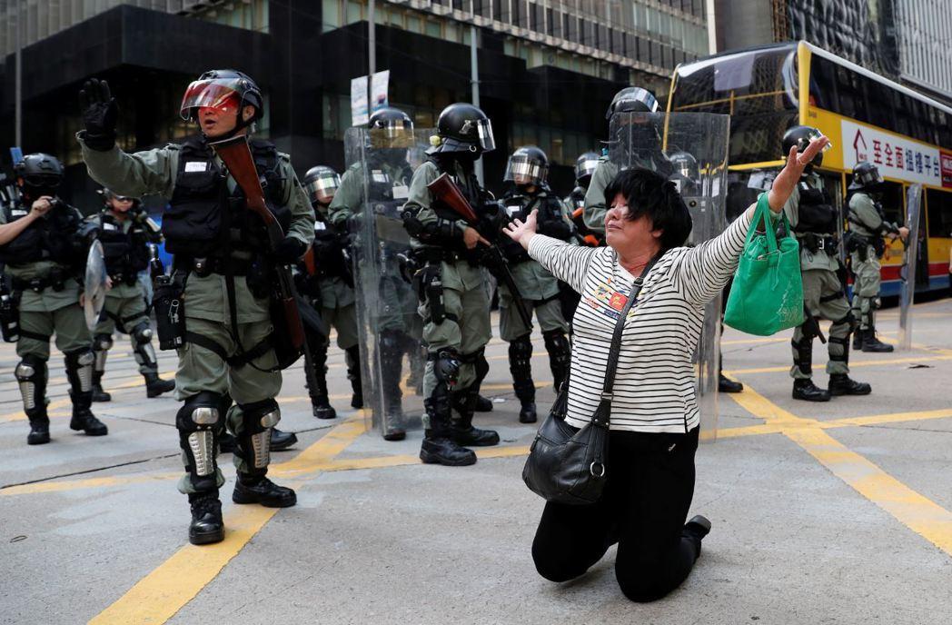 11月12日,一名香港市民下跪向防暴警察求情。 圖/路透社