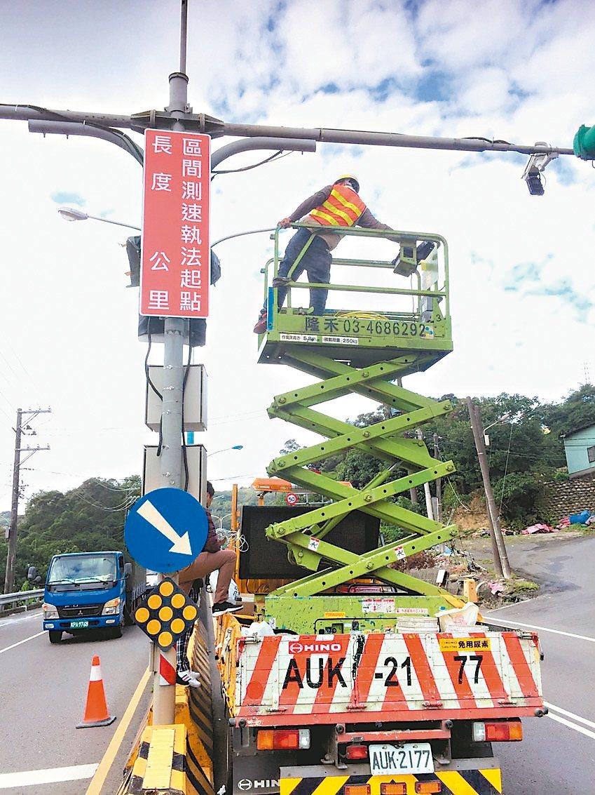 桃園市政府交通局在龜山區試辦區間平均速率執法,工程人員近日在出入口安裝明顯標誌,...