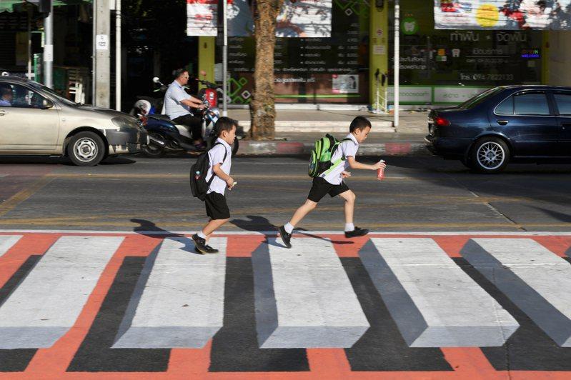 泰國曼谷一處學校大門外繪製了3D「漂浮」斑馬線,利用錯覺讓駕駛放慢速度。 路透社