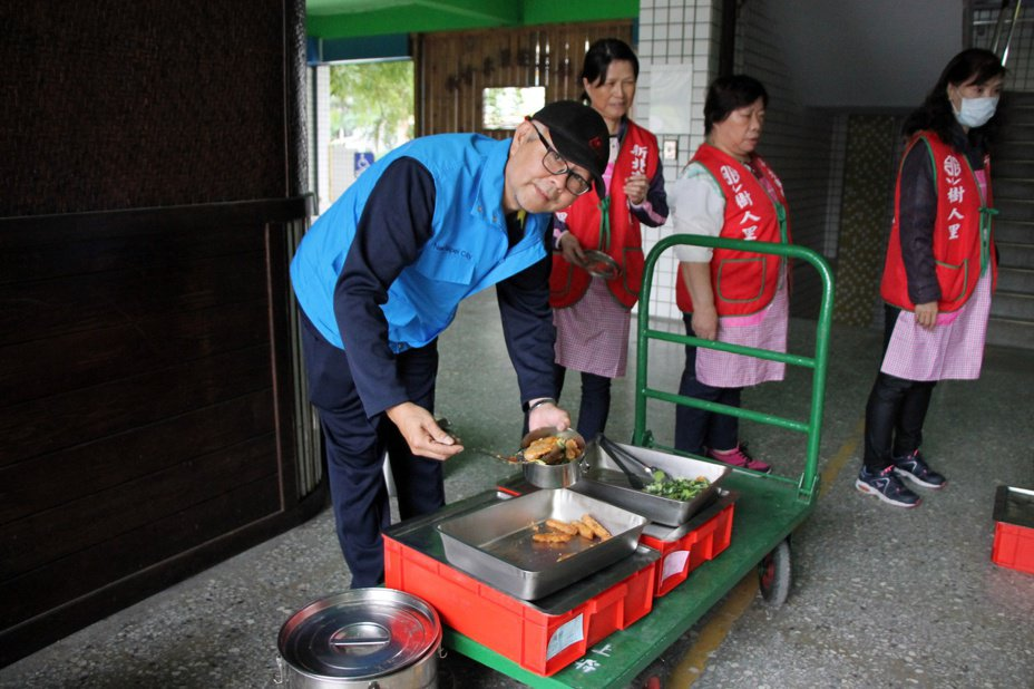 為推廣剩食再利用,樹人里長邱世昌(左)將學校剩下的營養午餐分送給里內獨居老人。圖/新北市民政局提供