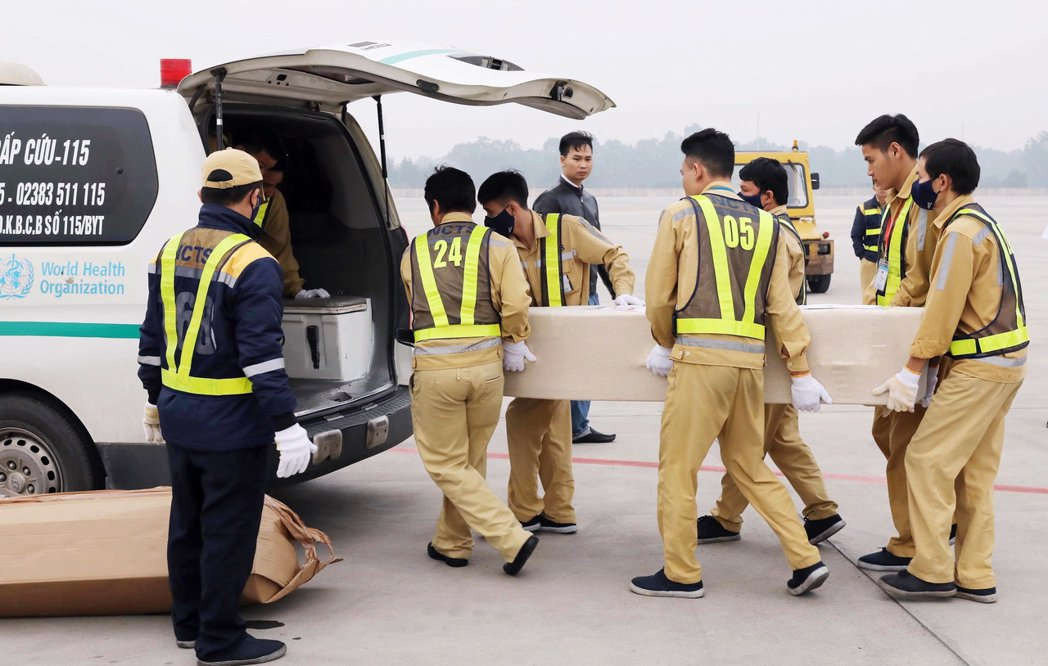官員在越南河內內排國際機場卸下裝有英國貨櫃屍案罹難者遺體的棺材。(歐新社)