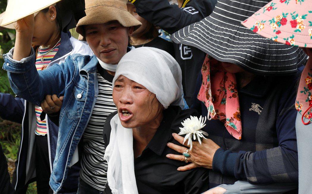 裴氏南的母親(中)在女兒的遺體由救護車運抵家鄉越南義安省時,哭得肝腸寸斷。(路透...