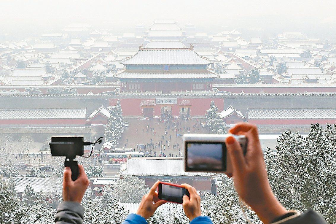 遊客擠在景山遠眺初雪後的故宮。 (新華社)